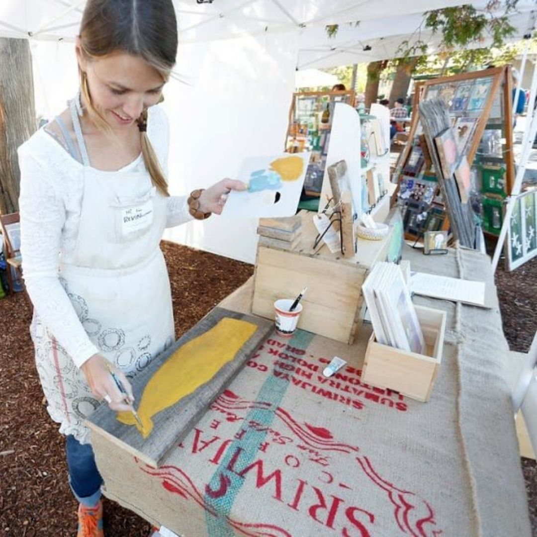 Photo of a woman painting a wooden plank at the Freeport Fall Festival in Freeport, Maine.