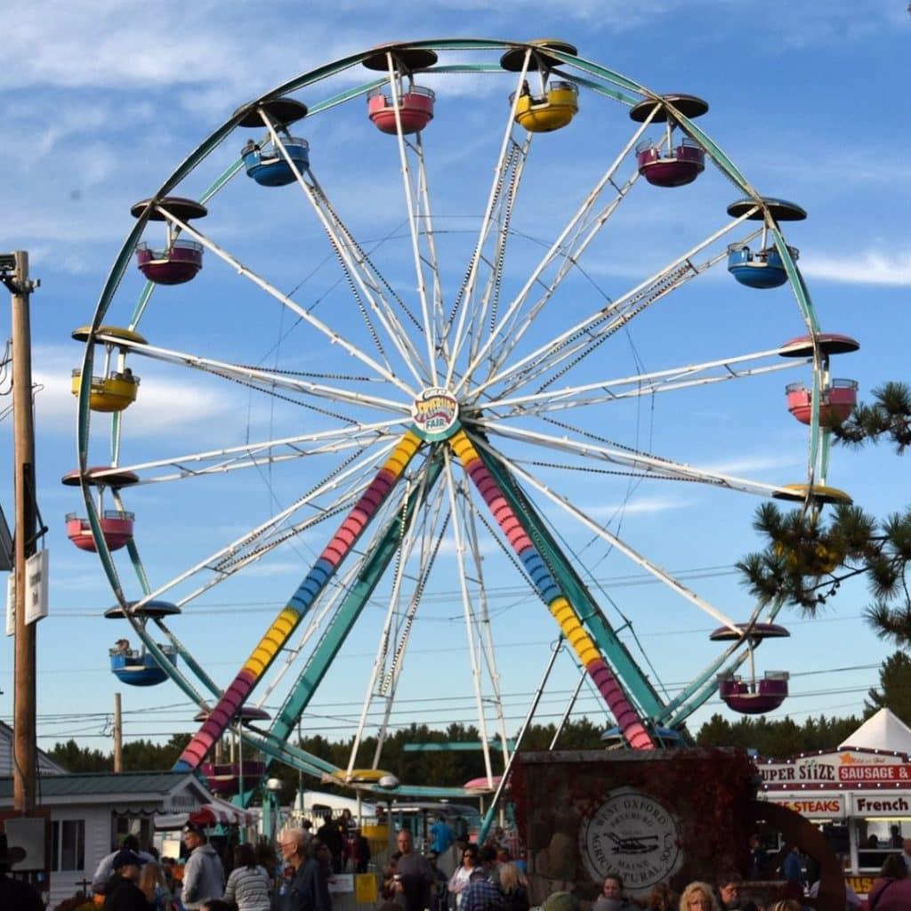 Photo of a colorful ferris wheel at a fair.