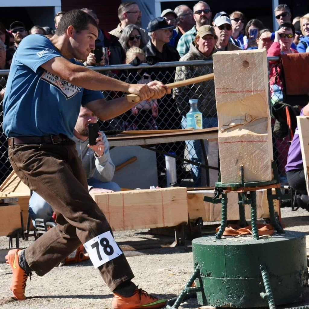 Closeup of a man competing in a lumberjack chopping contest.
