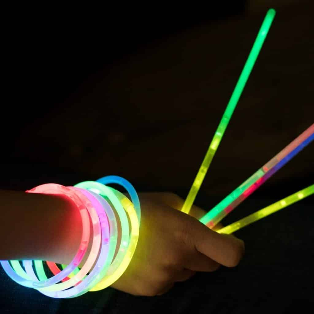 Closeup of a person wearing glowstick bracelets and holding a few glow sticks.