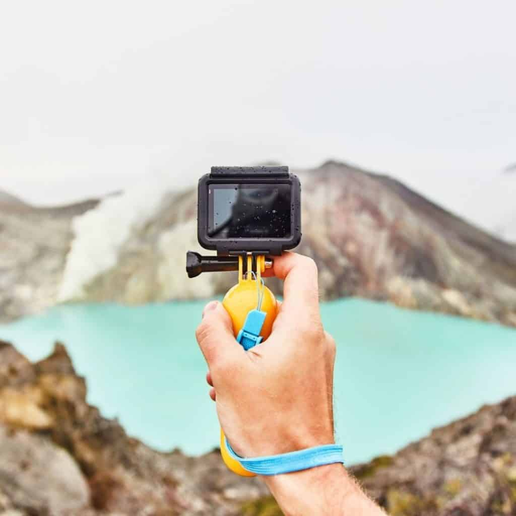 Closeup of a hand holding up a GoPro camera with mountains in the background.