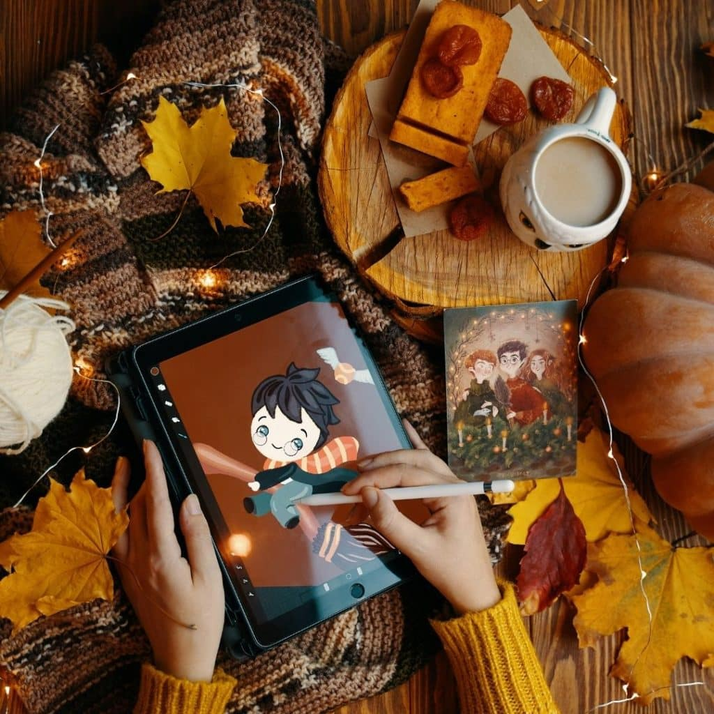 Top-down photo of a person drawing Harry Potter with Fall decor arranged on the table.