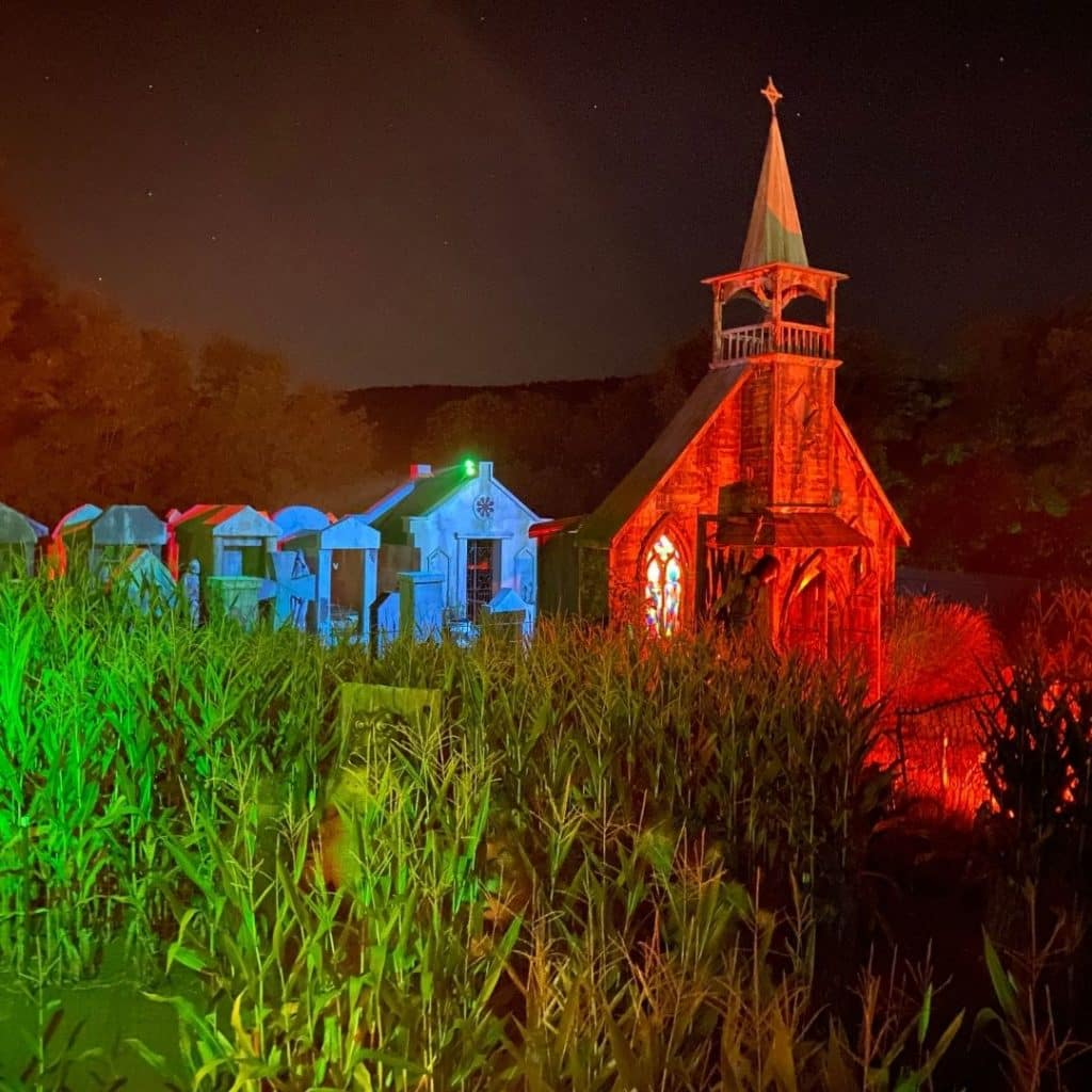 Photo of the outside of a haunted house setup next to a corn field at night.