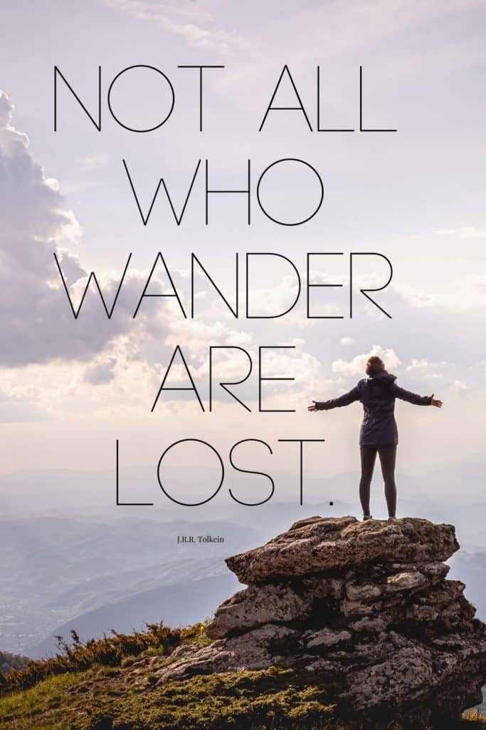 """Photo of a woman standing on a larger rock posing triumphantly. Text overlay reads """"Not all who wander are lost."""""""