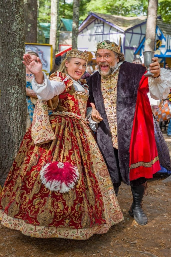 Photo of a man and a woman dressed in opulent Renaissance garb at King Richard's Faire in Massachusetts.