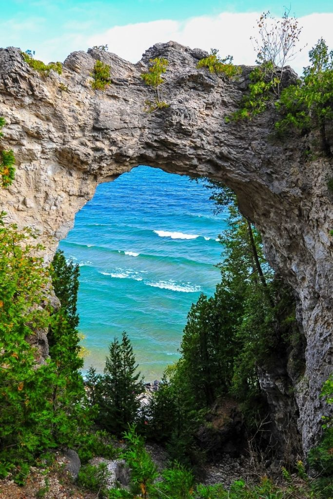 Photo of a rock arch with a lake in the background on Mackinac Island in Michigan.