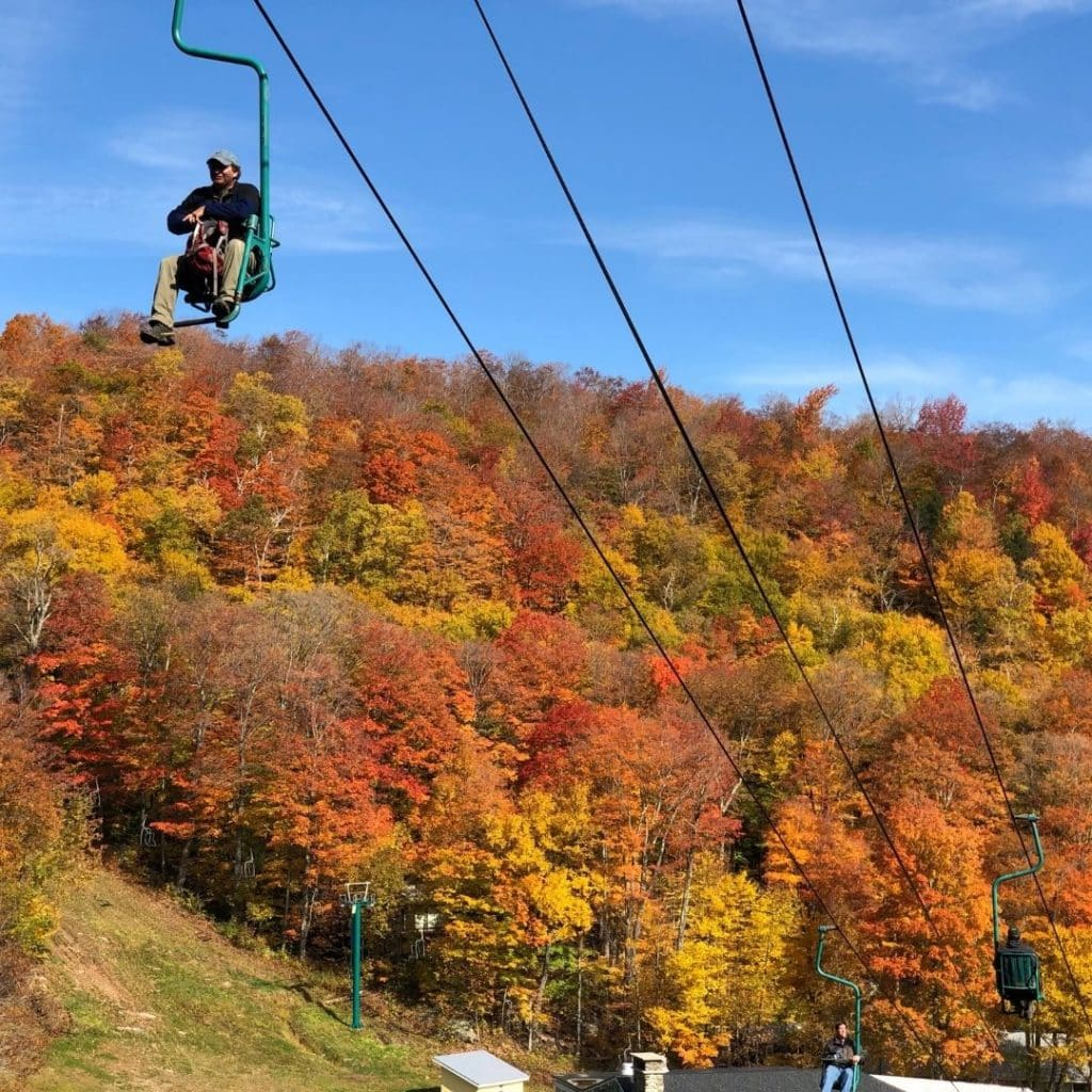 Photo of a man riding a ski lift with Fall foliage in the background.