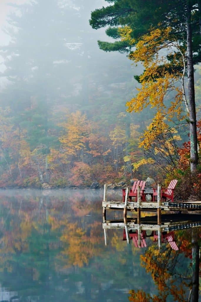 Photo of 2 red Adirondack style chairs sitting on a doc over a lake with Fall foliage surrounding it.