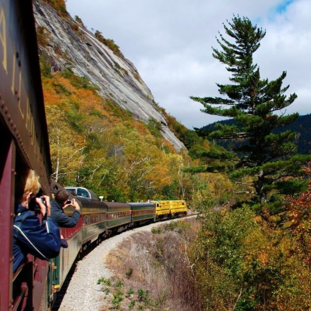 Photo of a train driving past a mountain covered in Fall foliage.