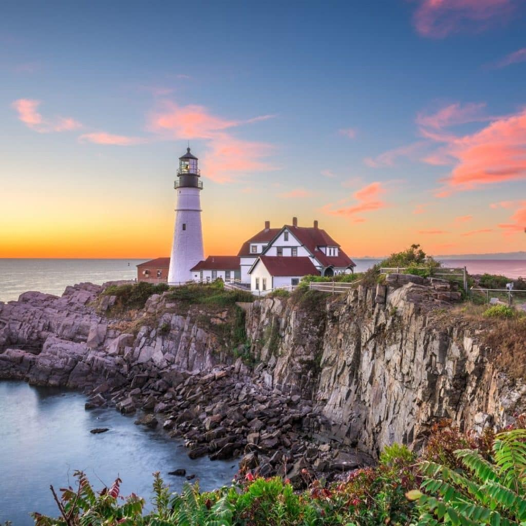 Photo of a lighthouse on a cliff in Portland during sunset.