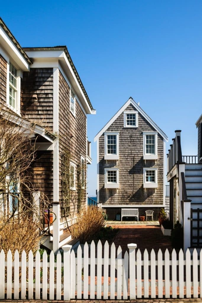 Photo of 2 wood-shingled beach houses in Provincetown, Massachusetts from the road.