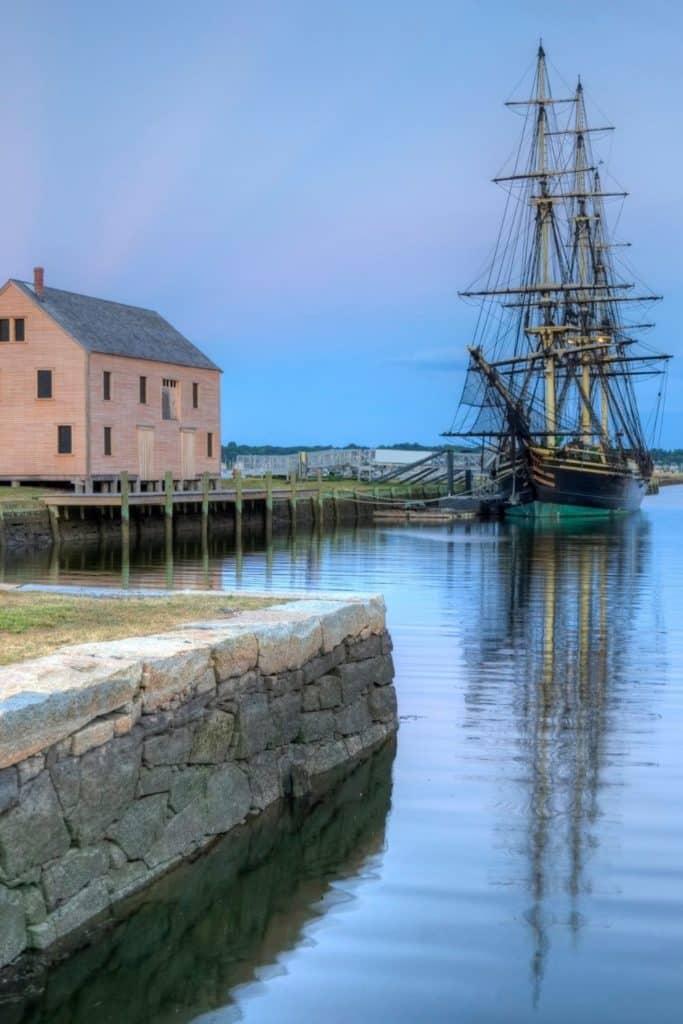 Photo of a historic house and sailing ship along the Salem, Massachusetts harbor.
