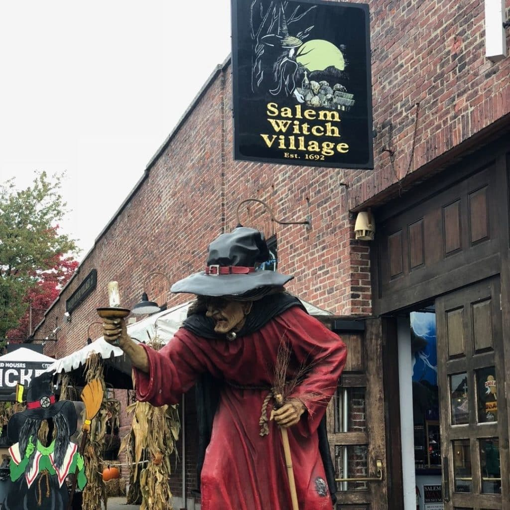 Photo of signage and decor outside the Salem Witch Village, including a large witch statue.