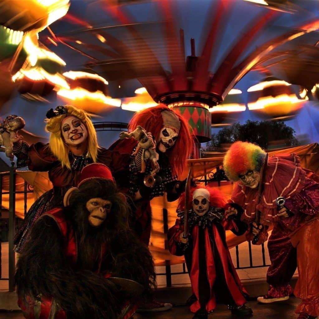 Photo of creepy clowns posing near an amusement park ride.