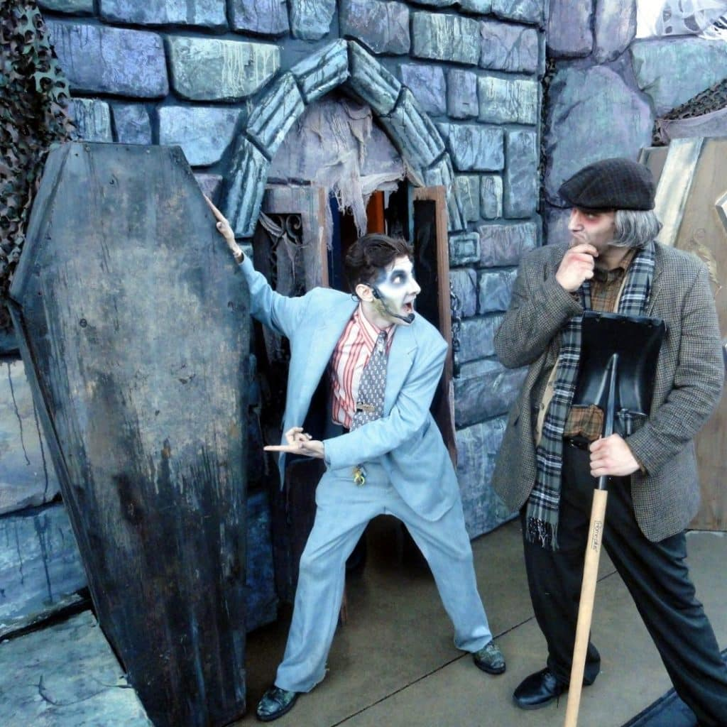Photo of 2 actors dressed as ghosts, acting out a scene with a coffin and a shovel.