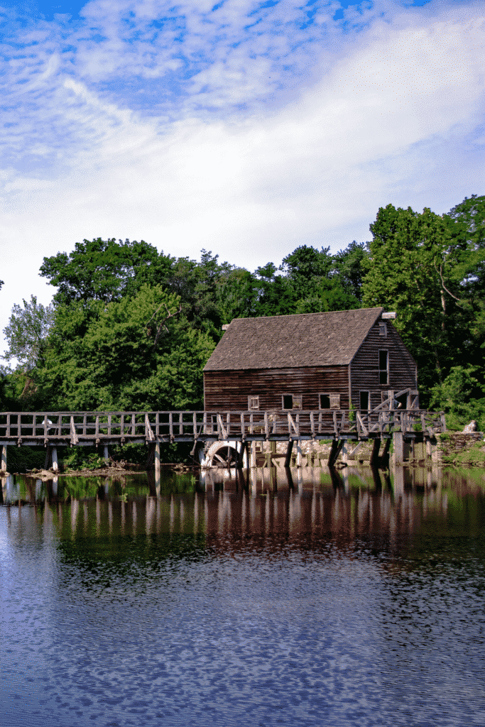 Photo of a wooden house with a water wheel and bridge.