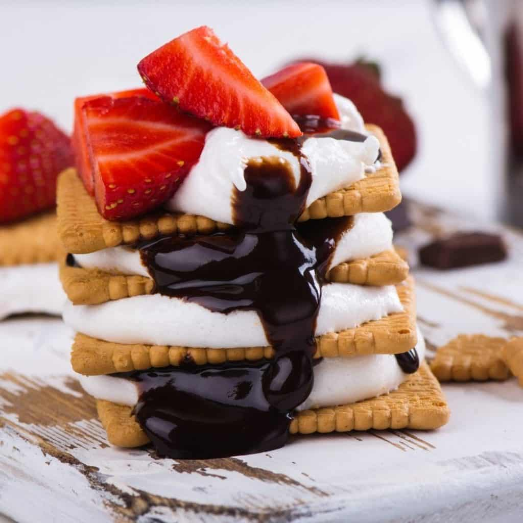 Closeup of a 3 layer smores with strawberries on top.