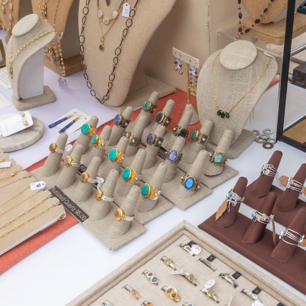 Closeup of a table with many different handmade jewelry displays, such as rings and necklaces.