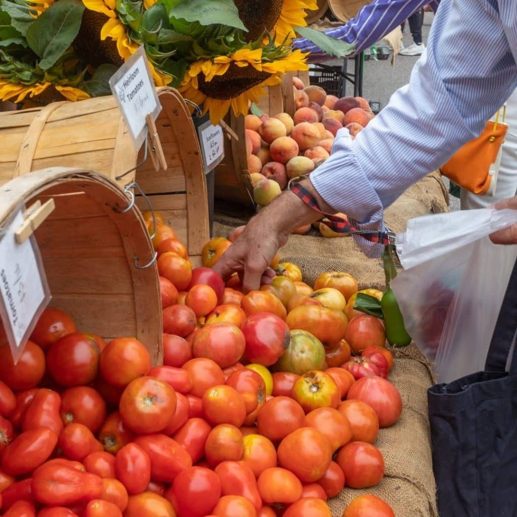 Closeup of a table with fresh produce, like tomatoes, peaches, and sunflowers, spilling out of wooden buckets.