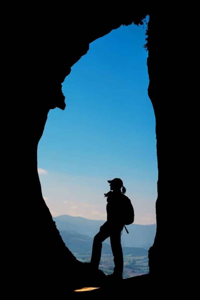Photo of a silhouette of a woman with a backpack standing in an opening between rocks.