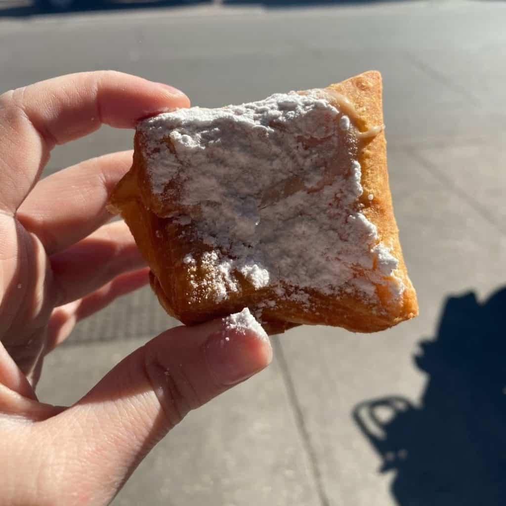 Closeup of a beignet with powdered sugar.