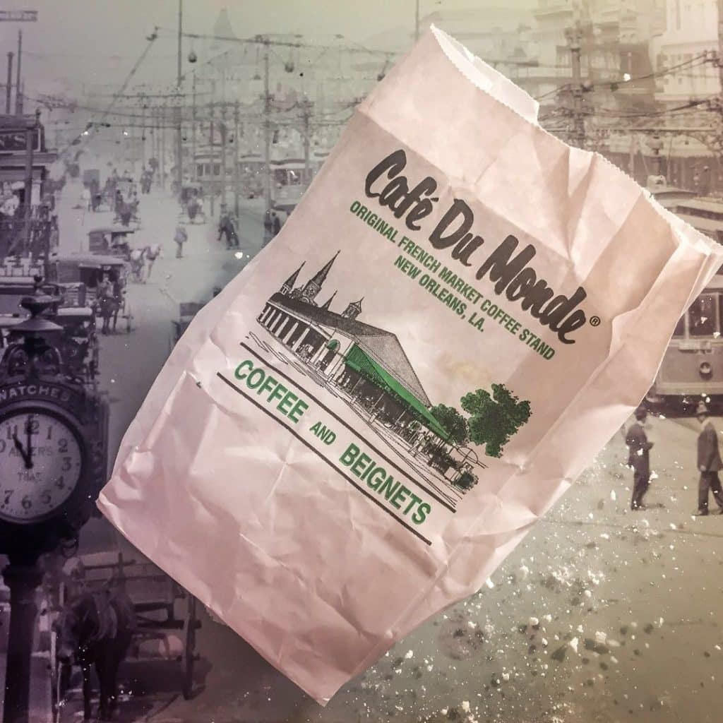 Flat lay photo of a bag of beignets from Café Du Monde with powdered sugar all over the table.