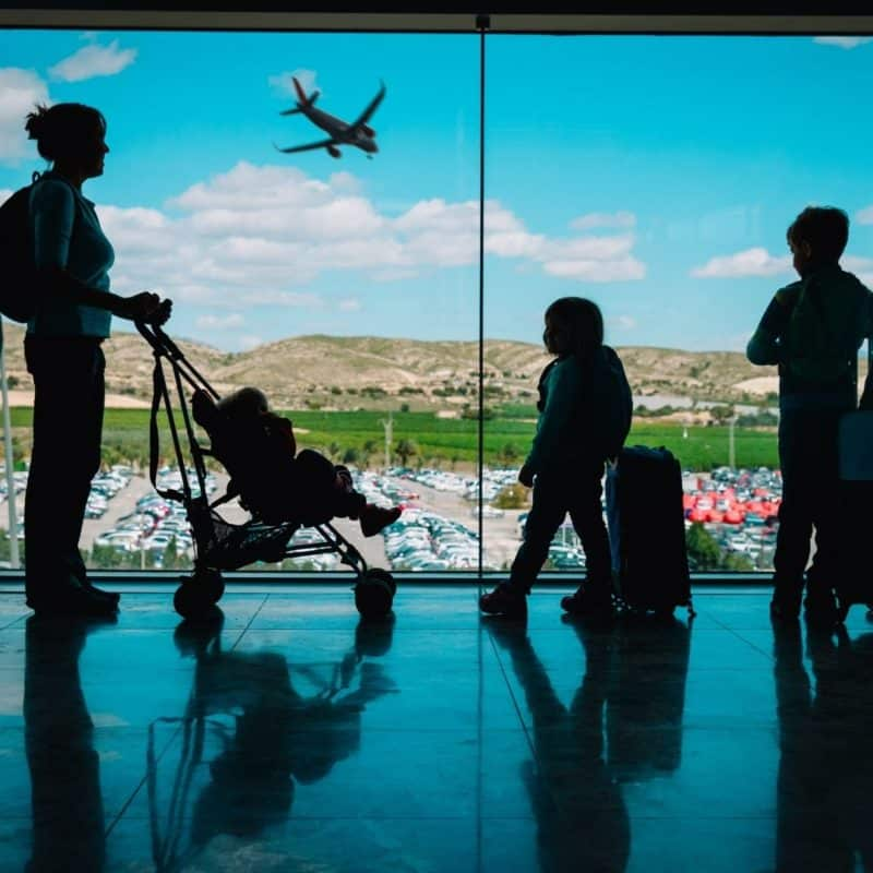 Photo of a family with kid at an airport, looking out the window at a plane.