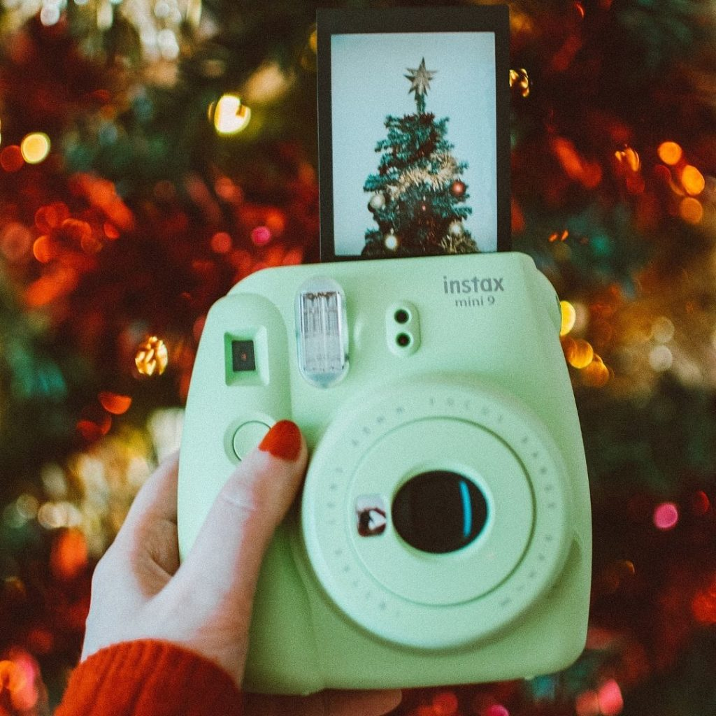 Photo of a person holding a green Instax camera with a photo of a Christmas tree popping out and Christmas lights in the background.
