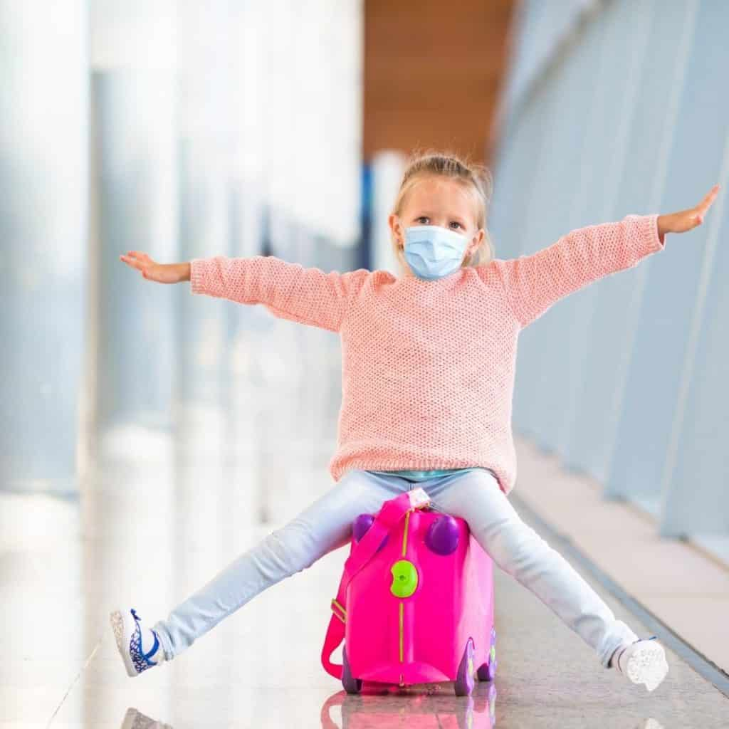 Photo of a young girl on a ride on suitcase.