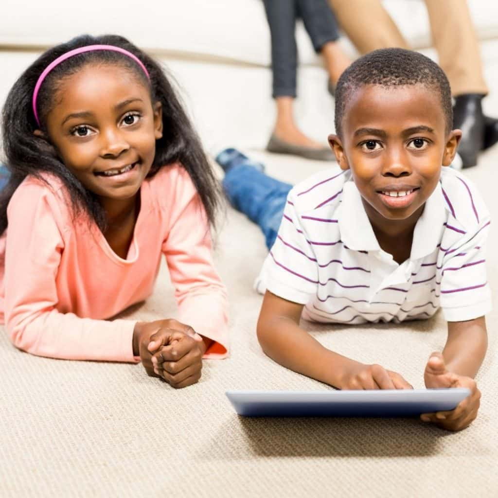 Photo of two kids laying on a carpet, looking at a tablet.