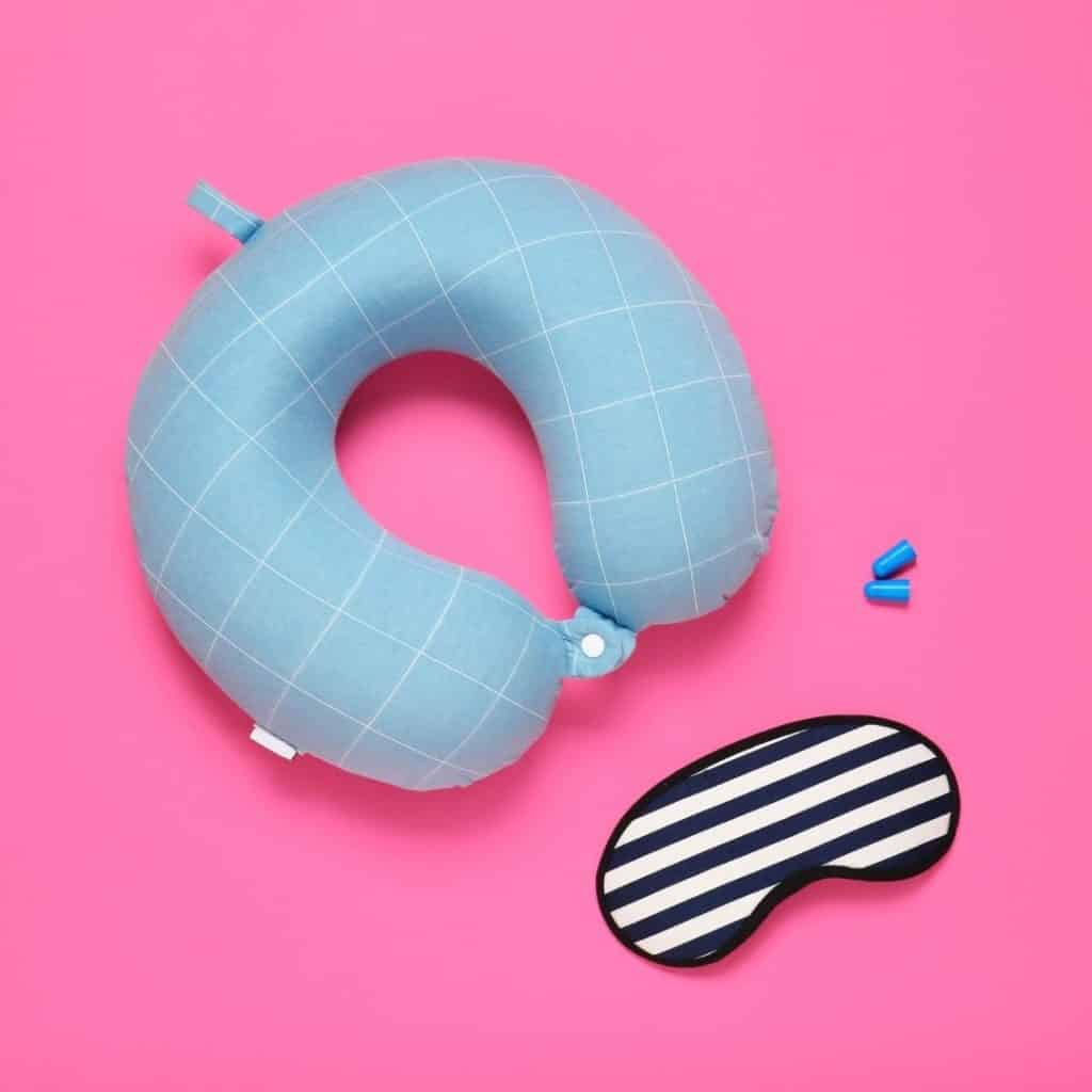 Flat lay photo of a neck pillow, sleep mask, and ear plugs on a pink surface.