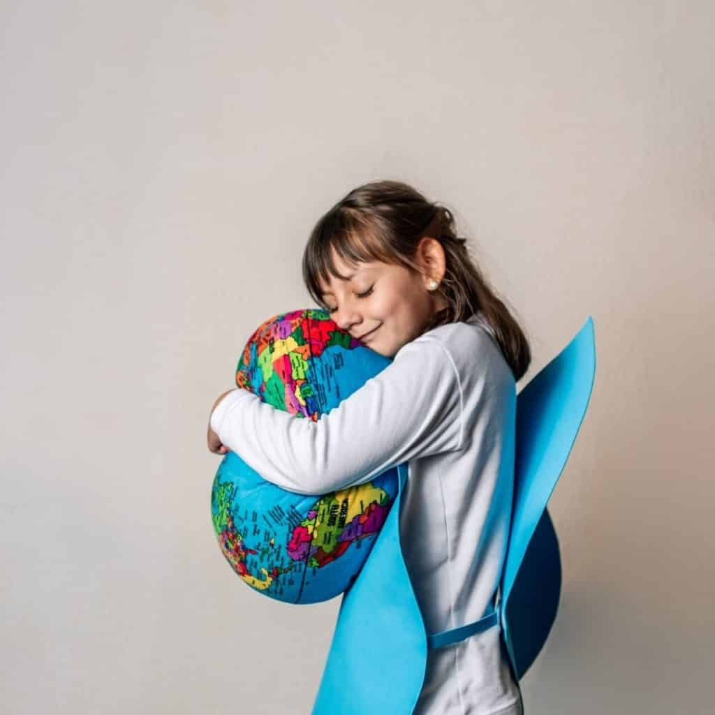 Photo of a young girl hugging a squishy world globe.