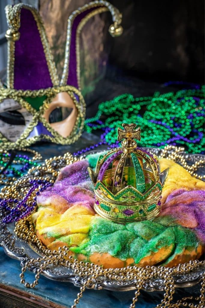 Photo of a Mardi Gras King Cake with a crown in the middle and lots of beads and masks in the background.
