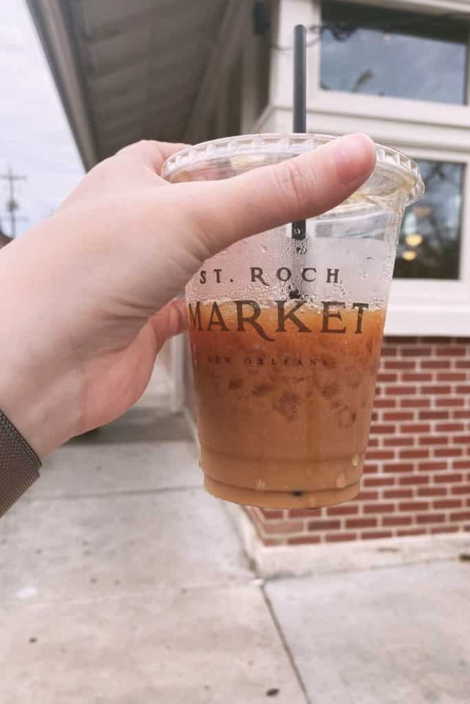 Photo of a person holding a cup of iced coffee from St. Roch Market in New Orleans.