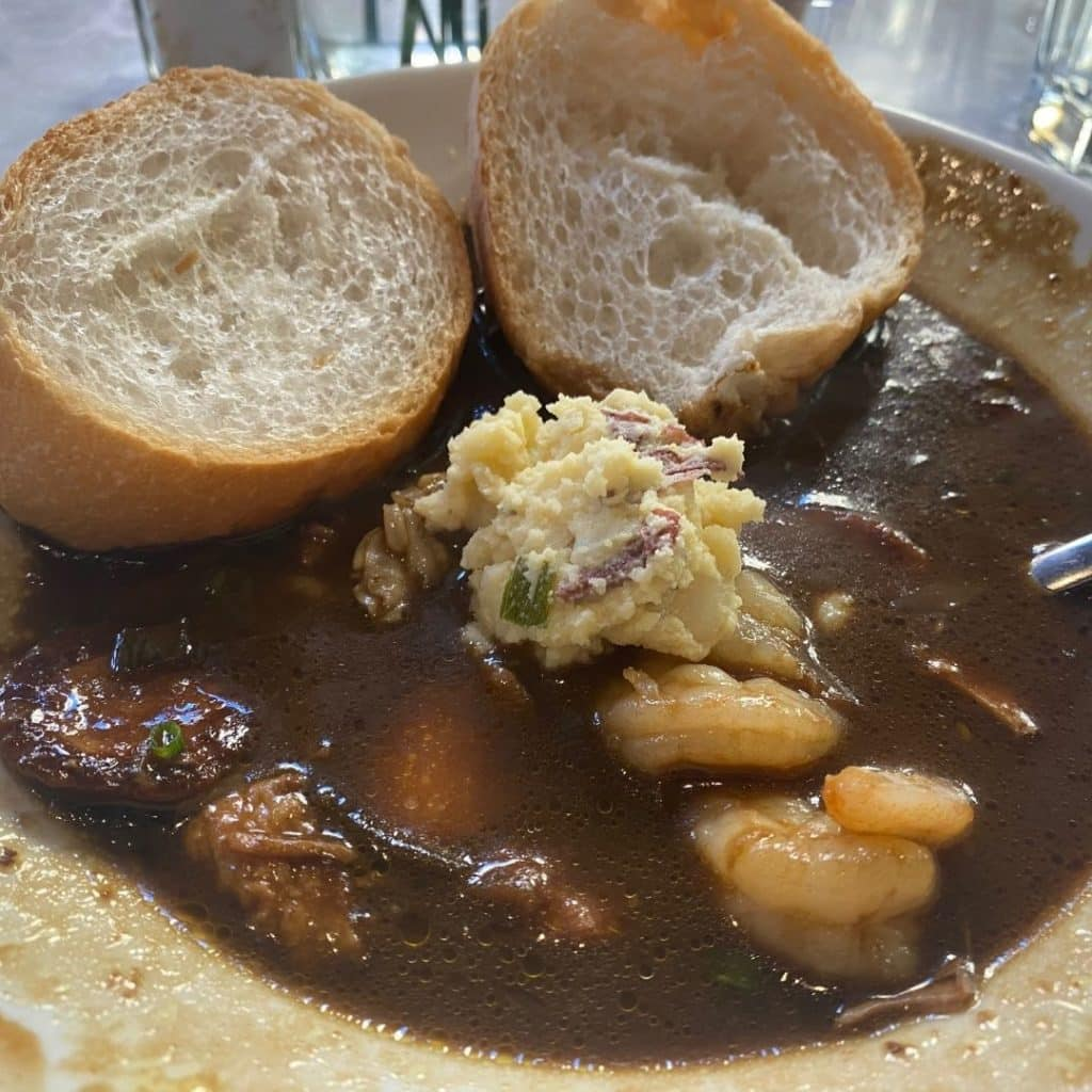 Closeup of a bowl of New Orleans gumbo with potato salad and bread on the side.