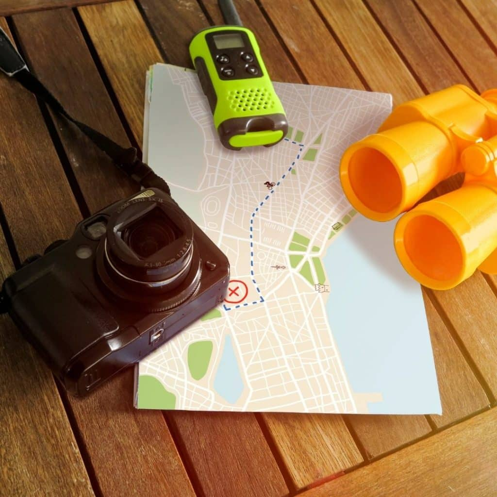 Photo of a map, camera, binoculars, and walkie talkie.