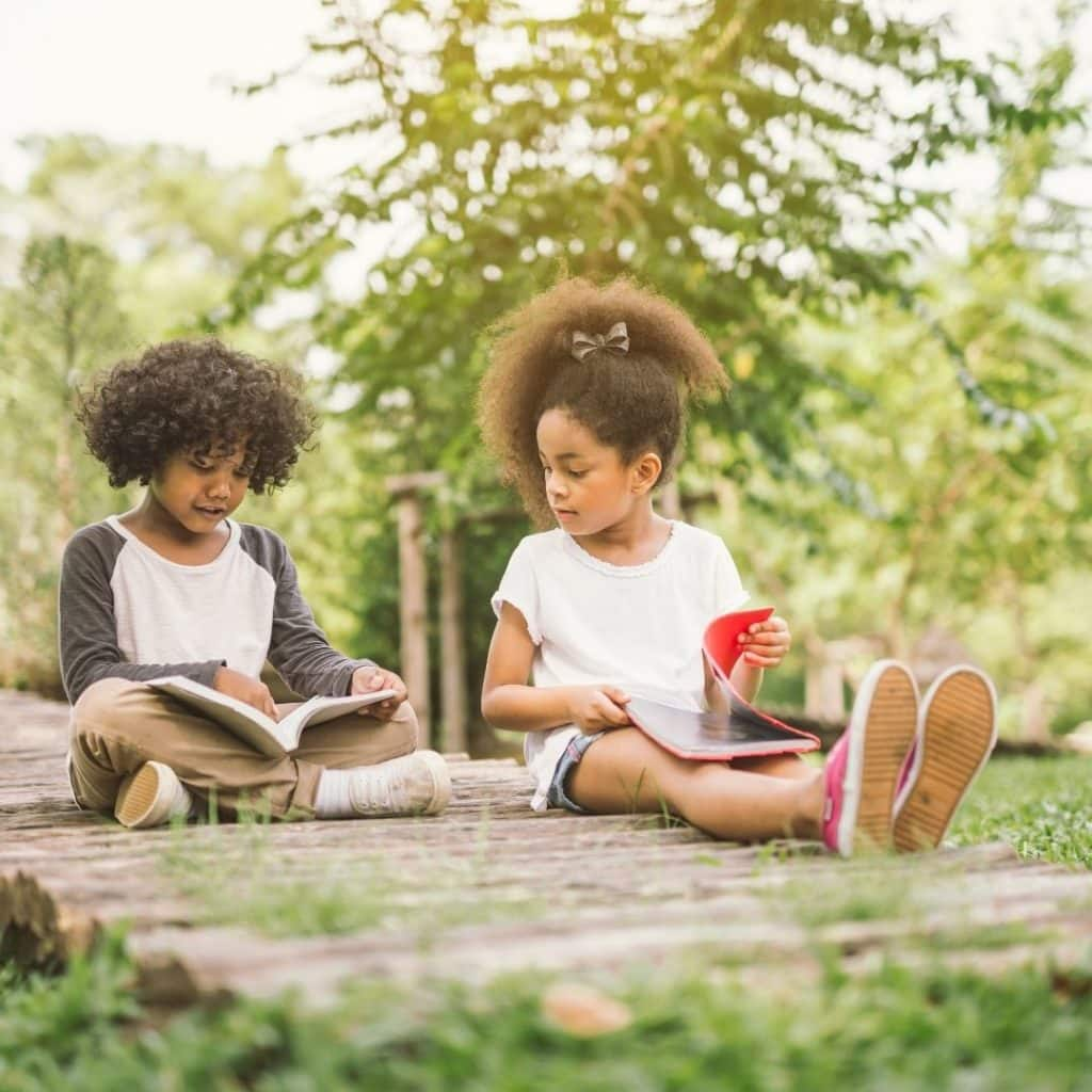 Photo of 2 young kids sitting on the ground, reading books.