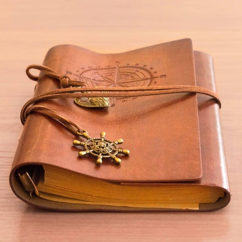 Closeup of a brown leather journal with a compass embossed on the cover.