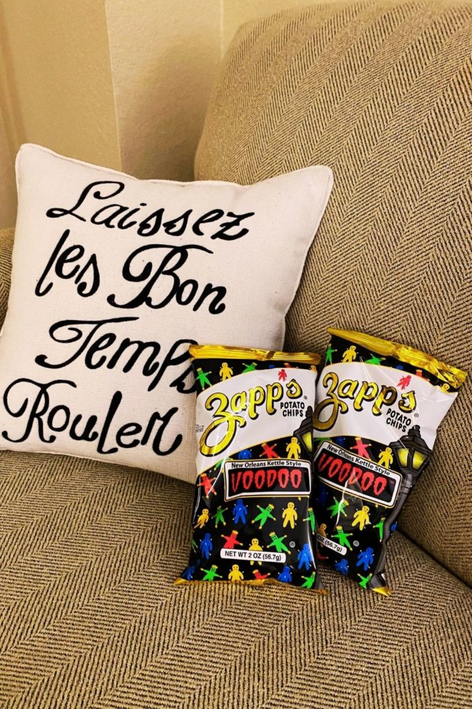 """Photo of 2 large bags of Zapp's Voodoo potato chips sitting on a couch next to a pillow that says """"Laissez les bon temps rouler."""""""